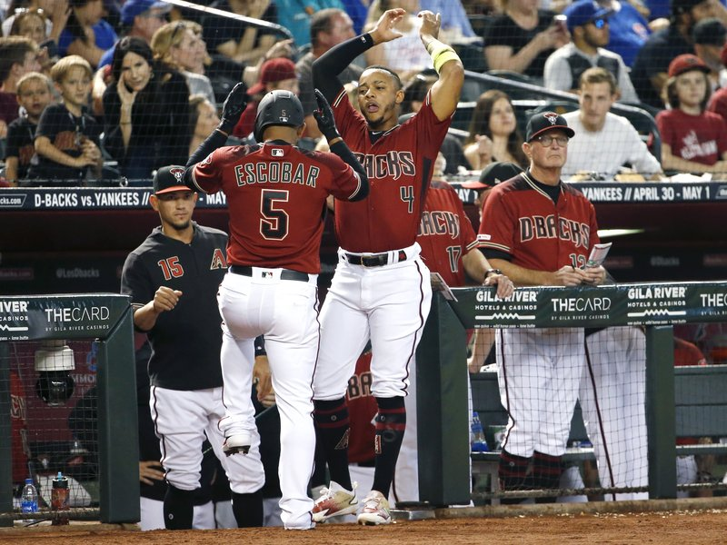 Arizona Diamondbacks' Eduardo Escobar (5) celebrates with teammate Ketel Marte (4) after hitting a solo home run against the Chicago Cubs during the fourth inning of a baseball game, Sunday, April 28, 2019, in Phoenix. (AP Photo/Ralph Freso)