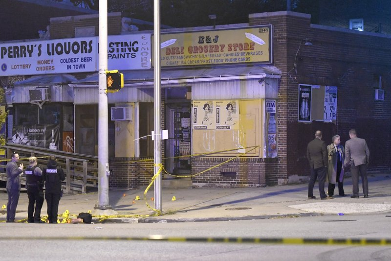 Police work near the scene of a shooting in Baltimore on Sunday, April 28, 2019. A gunman fired indiscriminately into a crowd that had gathered for Sunday cookouts on a Baltimore street, wounding several people including at least one of them fatally, the city's police commissioner said. (AP Photo/Steve Ruark)