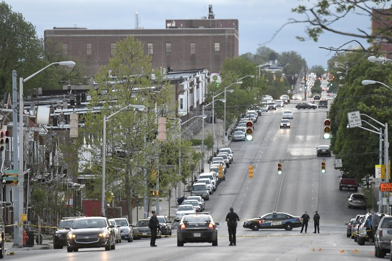 Police work near the scene where authorities say several people were shot, at least one fatally, Sunday, April 28, 2019, in Baltimore. (AP Photo/Steve Ruark)