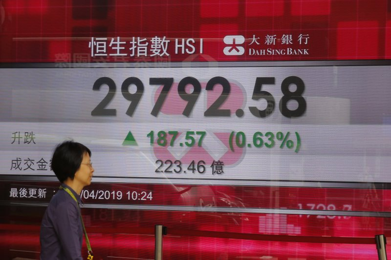 A women walks past an electronic board showing Hong Kong share index outside a bank in Hong Kong, Monday, April 29, 2019. (AP Photo/Kin Cheung)