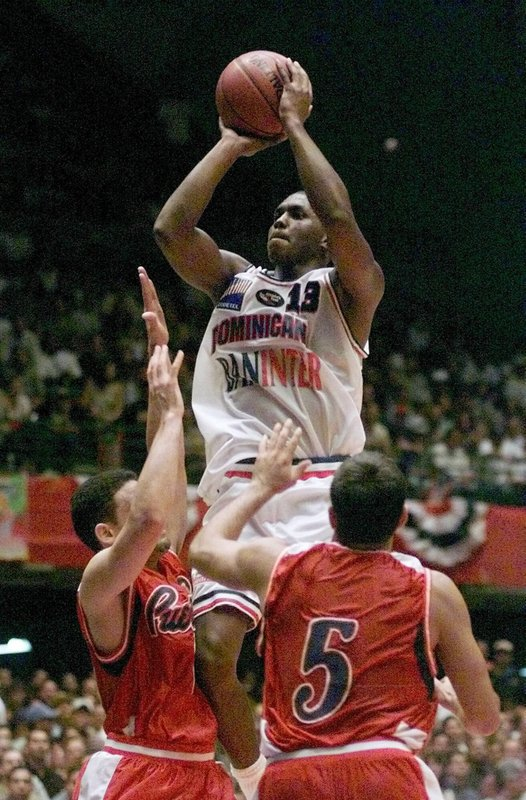 FILE - In this Sunday, July 18, 1999, file photo, the Dominican Republic's Felipe Lopez (13) gets above Puerto Rico defenders Eddie Casiano (5) and Edgar Padilla, left, as he shoots during the second half of an Olympic basketball qualifier, in San Juan, Puerto Rico. (AP Photo/Tony Gutierrez, File)