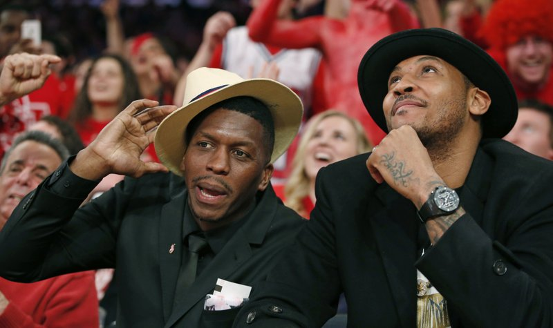 FILE - In this Sunday, Jan. 25, 2015, file photo, former St. Johns and NBA basketball player Felipe Lopez, left, sits beside then-New York Knicks forward Carmelo Anthony as they watch the first half of an NCAA college basketball game between St. (AP Photo/Kathy Willens, File)