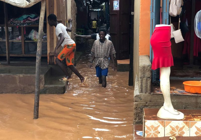 People walk through a flooded path leading to a shop during floods due to heavy rain in Pemba, Mozambique, Sunday , April 28, 2019. (AP Photo/Tsvangirayi Mukwazhi)