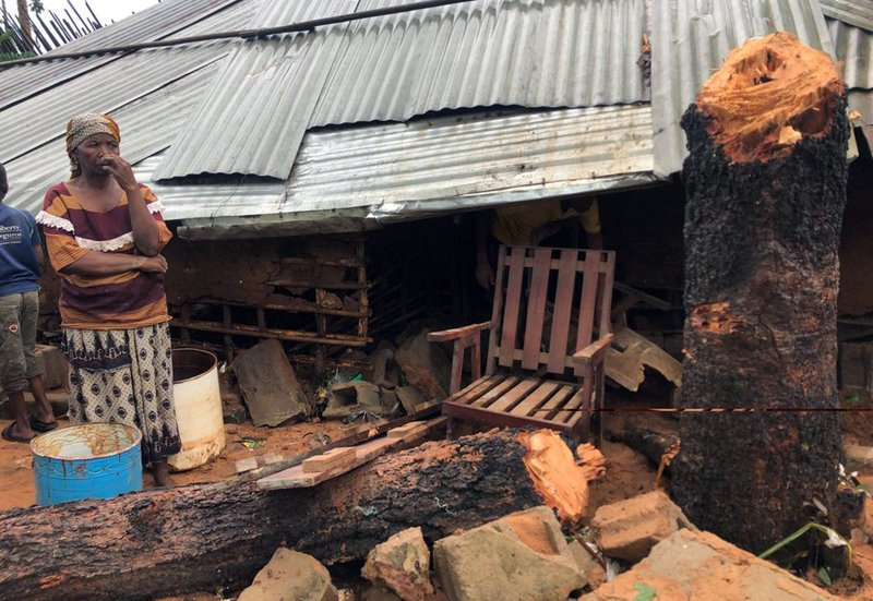 A woman stand next to a collapsed house where a neighbour was killed due to heavy rains in Pemba, Mozambique, Sunday , April 28, 2019. (AP Photo/Tsvangirayi Mukwazhi)
