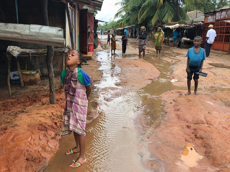 A child drinks water from a gutter during floods due to heavy rains in Pemba, Mozambique, Sunday, April 28, 2019. (AP Photo/Tsvangirayi Mukwazhi)
