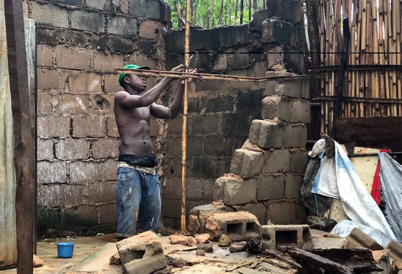 A man repairs a structure that collapsed due to heavy rains in Pemba, Mozambique, Sunday, April 28, 2019. (AP Photo/Tsvangirayi Mukwazhi)