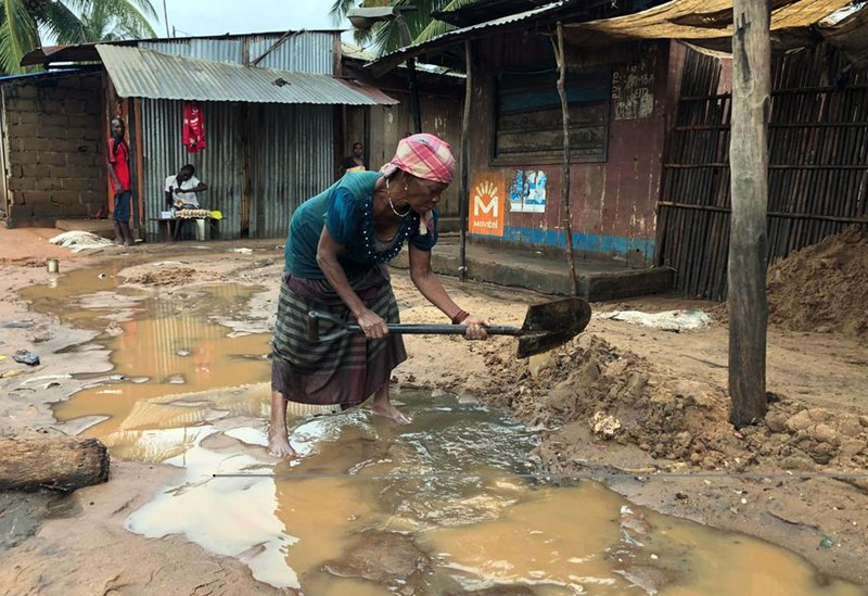 An elderly woman creates a drainage system near her shop to clear away floodwaters due to heavy rains in Pemba, Mozambique, Sunday, April 28, 2019. (AP Photo/Tsvangirayi Mukwazhi)