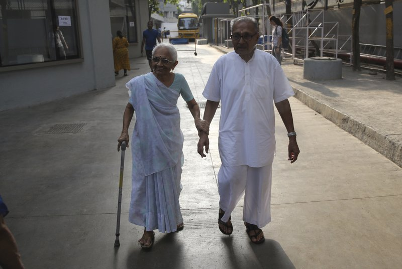 An elderly Indian couple leave a polling center after casting their votes during the fourth phase of general elections in Mumbai, India, Monday, April 29, 2019. (AP Photo/Rafiq Maqbool)