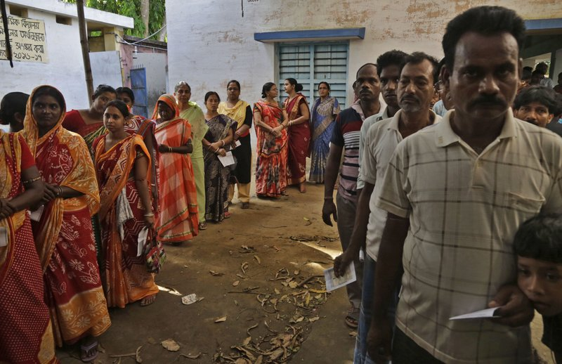 Indian men and women stand in queue to cast their votes at a polling booth in Bardhaman east constituency, West Bengal state, India, Monday, April 29, 2019. (AP Photo/Bikas Das)
