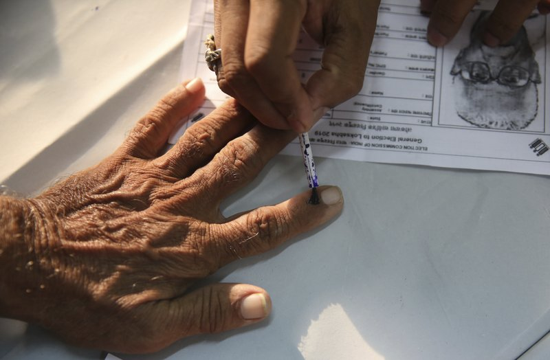 An elderly Indian citizen gets ink mark on his finger prior to voting at a polling center during  the fourth phase of general elections in Mumbai, India, Monday, April 29, 2019. (AP Photo/Rafiq Maqbool)