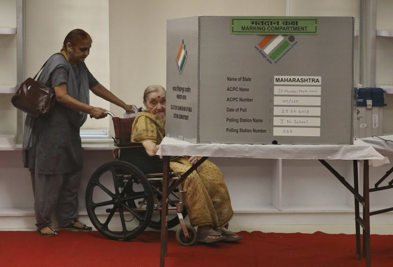 An elderly Indian citizen on a wheel chair casts her vote at a polling center during the fourth phase of general elections in Mumbai, India, Monday, April 29, 2019. (AP Photo/Rafiq Maqbool)