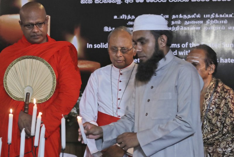 A Sri Lankan Muslim priest, lights a candle as Buddhist priest, left, Hindu priest, right, and Christian archbishop, center, watch during a function to express solidarity with all the victims of Easter Sunday attacks, in Colombo, Sri Lanka, Sunday, April 28, 2019. (AP Photo/Manish Swarup)