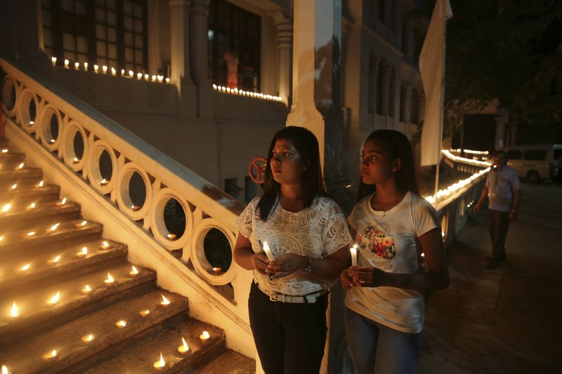 Sri Lankan girls hold candles during a function to express solidarity with all the victims of Easter Sunday attacks, in Colombo, Sri Lanka, Sunday, April 28, 2019. (AP Photo/Manish Swarup)