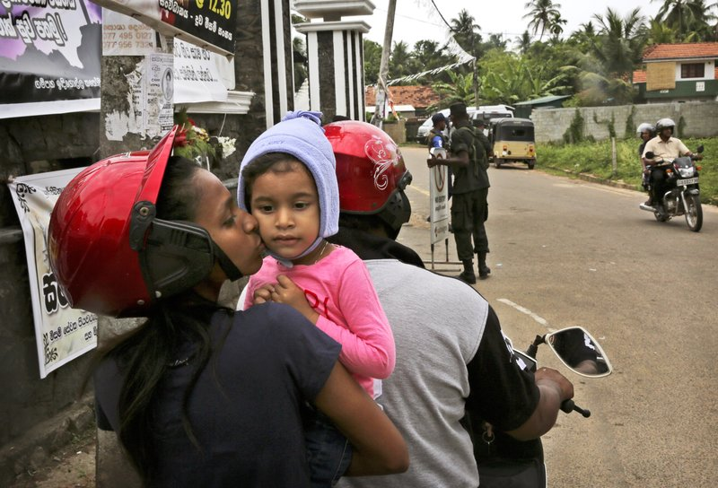 A Sri Lankan Christian mother kisses her daughter as they stop their two wheeler to have a look at the St. (AP Photo/Manish Swarup)