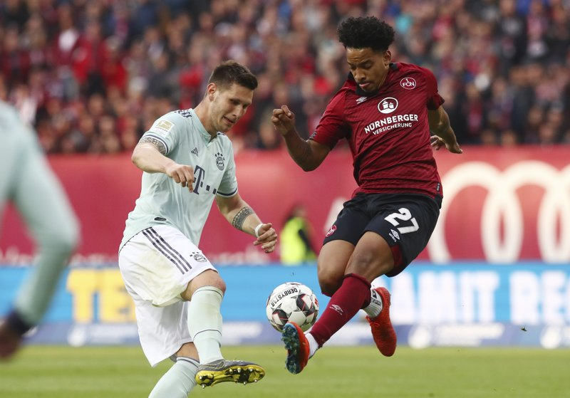 Nuremberg's Matheus Pereira, right, challenges for the ball with Bayern's Niklas Suele during the German Bundesliga soccer match between 1. (AP Photo/Matthias Schrader)