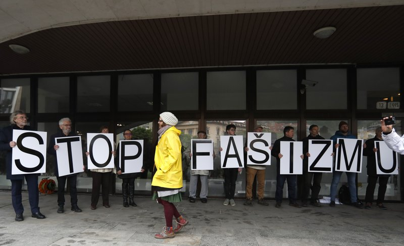 Protesters hold a banner outside the Supreme Court in Bratislava, Slovakia, Monday, April 29, 2019. The Supreme Court is considering a request from the Prosecutor General to ban parliamentary far-right party People's Party Our Slovakia. (AP Photo/Petr David Josek)