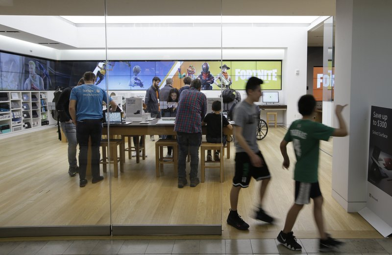In this March 21, 2019 photo passers-by depart an entrance to a Microsoft Store location, in Boston. U. (AP Photo/Steven Senne)