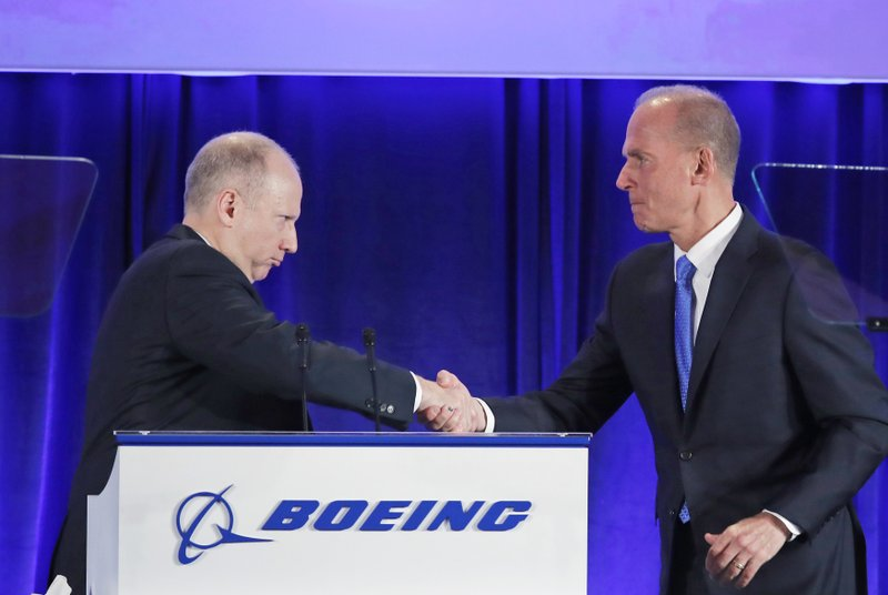 Boeing Vice-President and Corporate Secretary Grant Dixton, left, introduces Boeing Chief Executive Dennis Muilenburg during the company's annual shareholders meeting at the Field Museum in Chicago, Monday, April 29, 2019. (AP Photo/Jim Young, Pool)