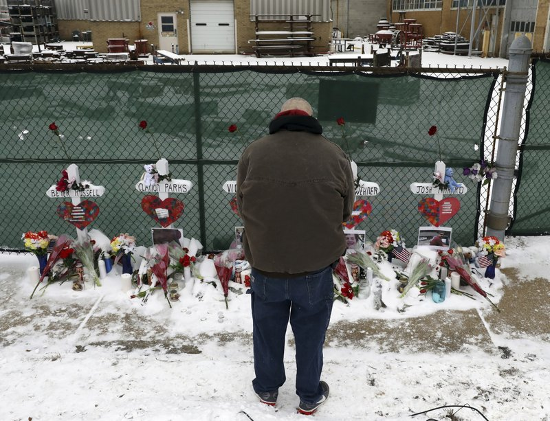 FILE - In this Feb. 17, 2019 file photo a man prays at a makeshift memorial placed for five victims near the warehouse of Henry Pratt Co. (AP Photo/Nam Y. Huh, File)