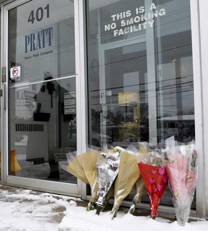 FILE - In this Feb. 17, 2019 file photo bouquets of flowers are placed for victims in front of the warehouse of Henry Pratt Co. (AP Photo/Nam Y. Huh, File)