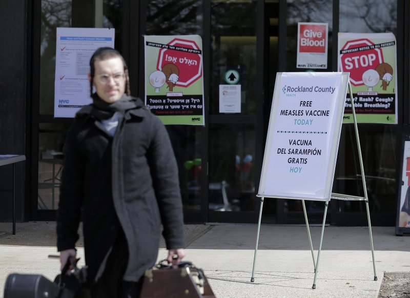 FILE - In this March 27, 2019 file photo, signs about measles and the measles vaccine are displayed at the Rockland County Health Department in Pomona, N. (AP Photo/Seth Wenig, File)