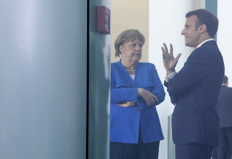 German Chancellor Angela Merkel, center, and the President of France Emmanuel Macron talks to each other during a meeting of Balkan leaders at the chancellery in Berlin, Monday, April 29, 2019. (AP Photo/Markus Schreiber)