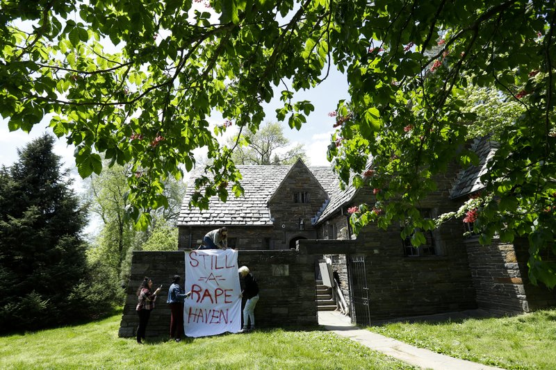 Swarthmore College students hang a banner near the Phi Psi fraternity house during a sit-in, Monday, April 29, 2019, in Swarthmore, Pa. (AP Photo)