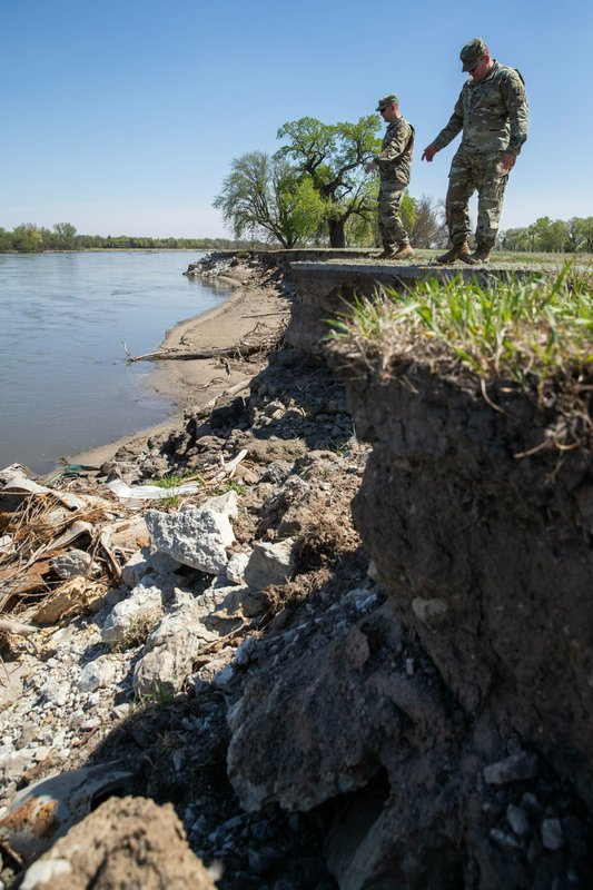 In this April 24, 2019, photo Shane M. Martin, a construction and facilities management officer and Major Scott Ingalsbe, State Public Affairs Officer both with the Nebraska Army National Guard stand close by the erosion caused by the flood along the Platte River  in Ashland, Neb. (Brendan Sullivan/Omaha World-Herald via AP)
