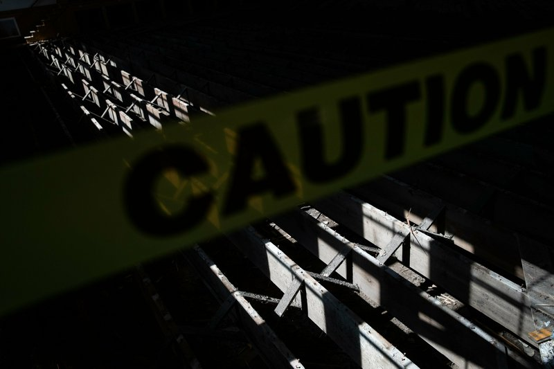 In this April 24, 2019, photo a caution sign is displayed near a damaged floor caused by recent flooding at Memorial Hall in Ashland, Neb. (Brendan Sullivan/Omaha World-Herald via AP)