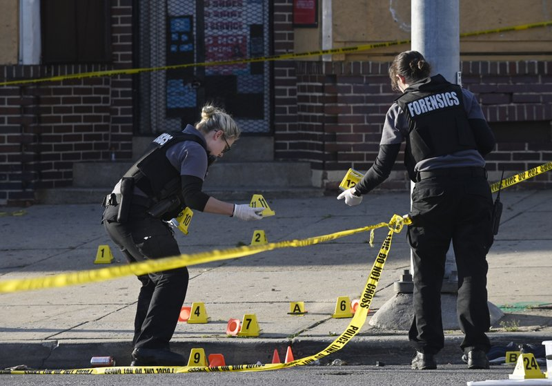 Baltimore police forensics officers place evidence markers next to bullet casings while investigating the scene of a shooting in Baltimore on Sunday, April 28, 2019. (Kenneth K. Lam/The Baltimore Sun via AP)