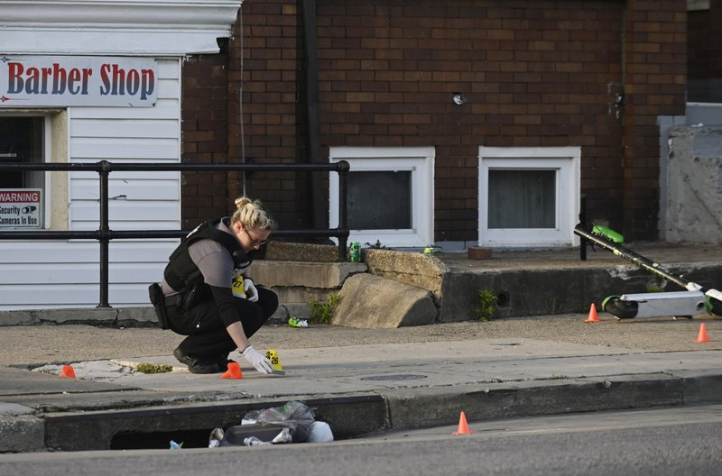 A Baltimore police forensics officer places an evidence marker next to a bullet casing while investigating the scene of a shooting in Baltimore on Sunday, April 28, 2019. (Kenneth K. Lam/The Baltimore Sun via AP)