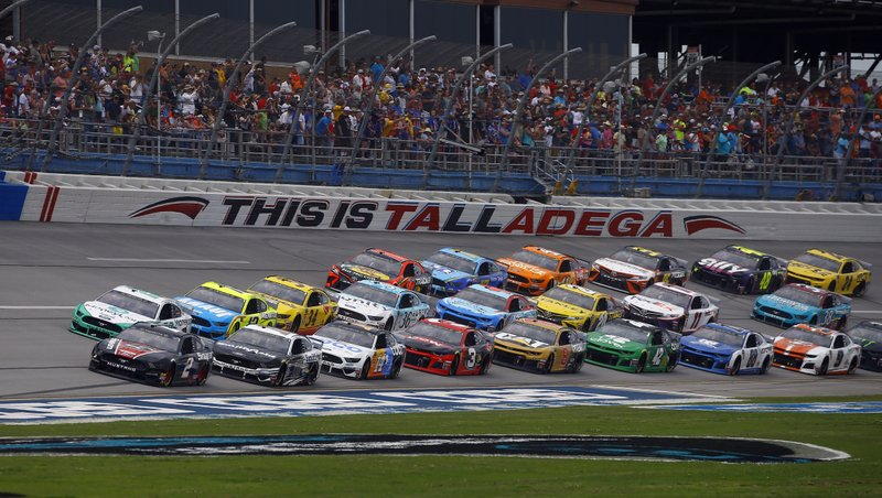 Brad Keselowski (2) leads a pack of cars through the trip oval during the NASCAR Cup Series auto race at Talladega Superspeedway, Sunday, April 28, 2019, in Talladega, Ala. (AP Photo/Butch Dill)