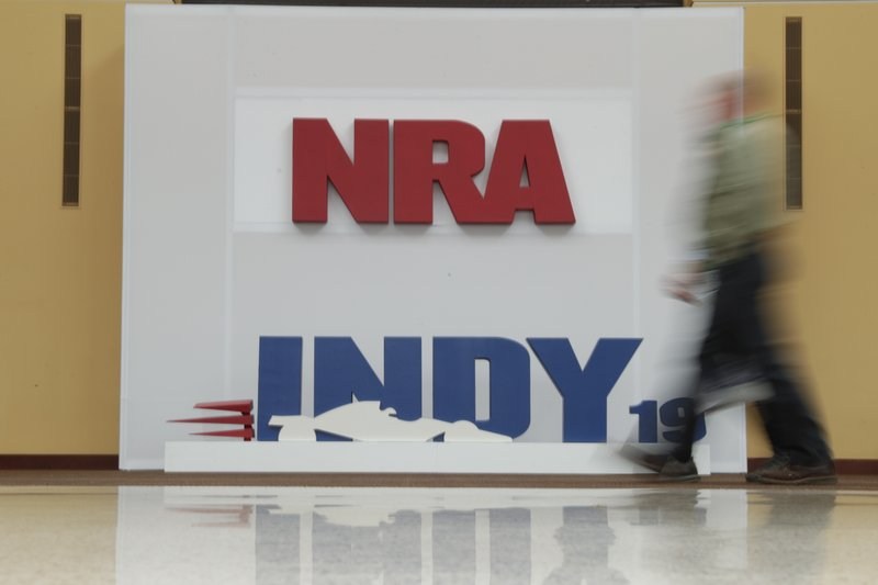 A visitor to the at the National Rifle Association Annual Meeting walks past signage for the event in Indianapolis, Saturday, April 27, 2019. (AP Photo/Michael Conroy)