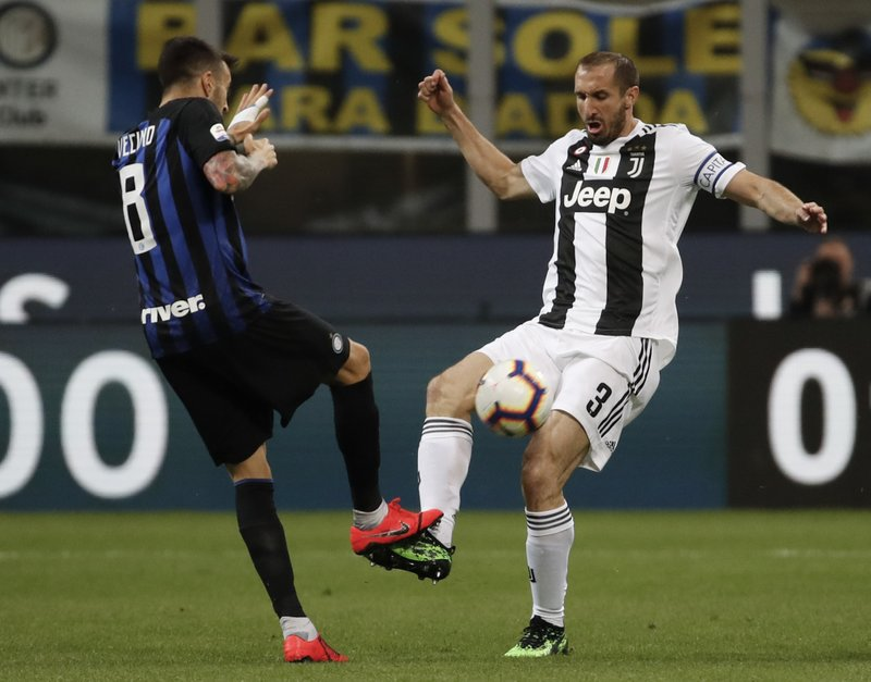 Inter Milan's Matias Vecino, left, and Juventus' Giorgio Chiellini fight for the ball during the Serie A soccer match between Inter Milan and Juventus at the San Siro Stadium, in Milan, Italy, Saturday, April 27, 2019. (AP Photo/Antonio Calanni)