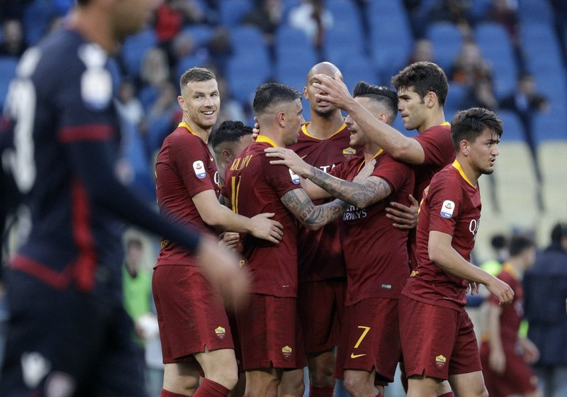 Roma's Aleksandar Kolarov, center, celebrates with his teammates after he scored his side's third goal during a Serie A soccer match between Roma and Cagliari, at Rome's Olympic Stadium, Saturday, April 27, 2019. (AP Photo/Gregorio Borgia)