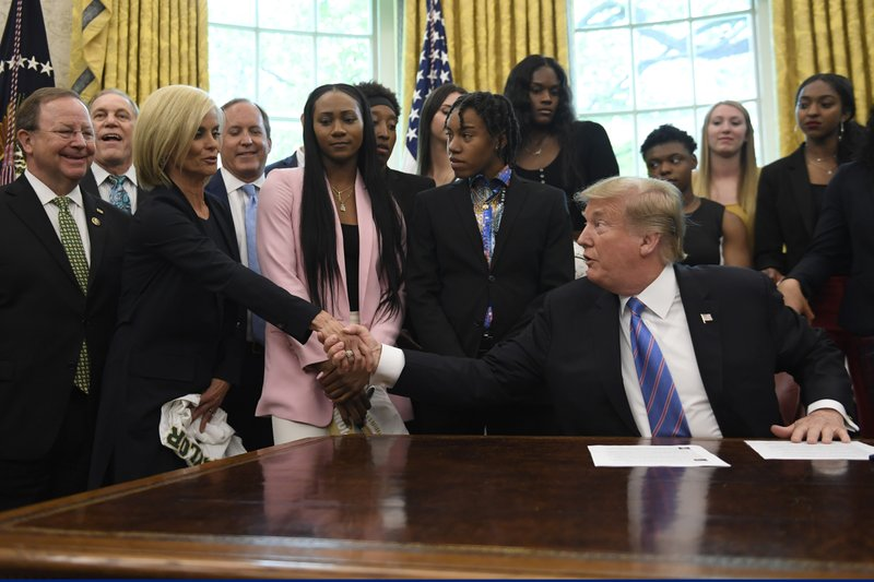 President Donald Trump shakes hands with Baylor women's basketball head coach Kim Mulkey, third from left, as he welcomed members of the Baylor women's basketball team, who are the 2019 NCAA Division I Women's Basketball National Champions, to the Oval Office of the White House in Washington, Monday, April 29, 2019. (AP Photo/Susan Walsh)