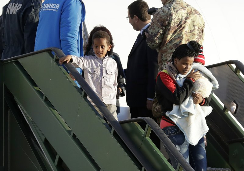 A woman holding a baby is followed by a child as they disembark from an Italian military aircraft arriving from Misrata, Libya, at Pratica di Mare military airport, near Rome, Monday, April 29, 2019. (AP Photo/Andrew Medichini)