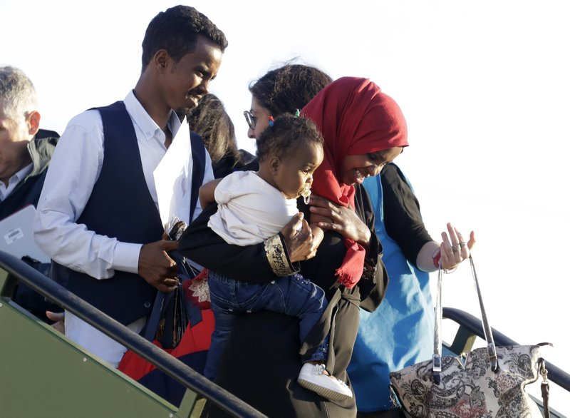 A family disembarks from an Italian military aircraft arriving from Misrata, Libya, at Pratica di Mare military airport, near Rome, Monday, April 29, 2019. (AP Photo/Andrew Medichini)