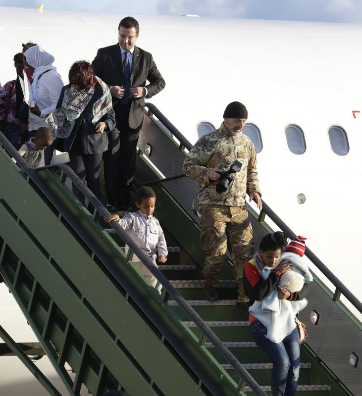 Italian Interior Ministry Undersecretary Stefano Candiani, top, adjusts his jacket as he stands on the steps while asylum seekers disembark from an Italian military aircraft which arrived from Misrata, Libya, at Pratica di Mare military airport, near Rome, Monday, April 29, 2019. (AP Photo/Andrew Medichini)
