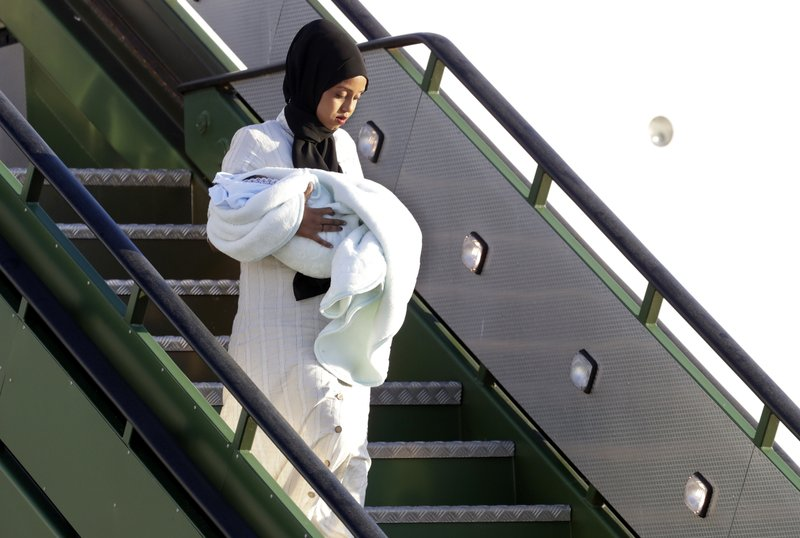 A woman holds a baby as she disembarks an Italian military aircraft arriving from Misrata, Libya, at Pratica di Mare military airport, near Rome, Monday, April 29, 2019. (AP Photo/Andrew Medichini)