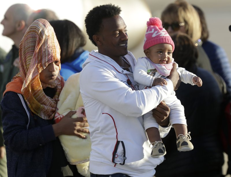 A family with a baby disembarks from an Italian military aircraft arriving from Misrata, Libya, at Pratica di Mare military airport, near Rome, Monday, April 29, 2019. (AP Photo/Andrew Medichini)