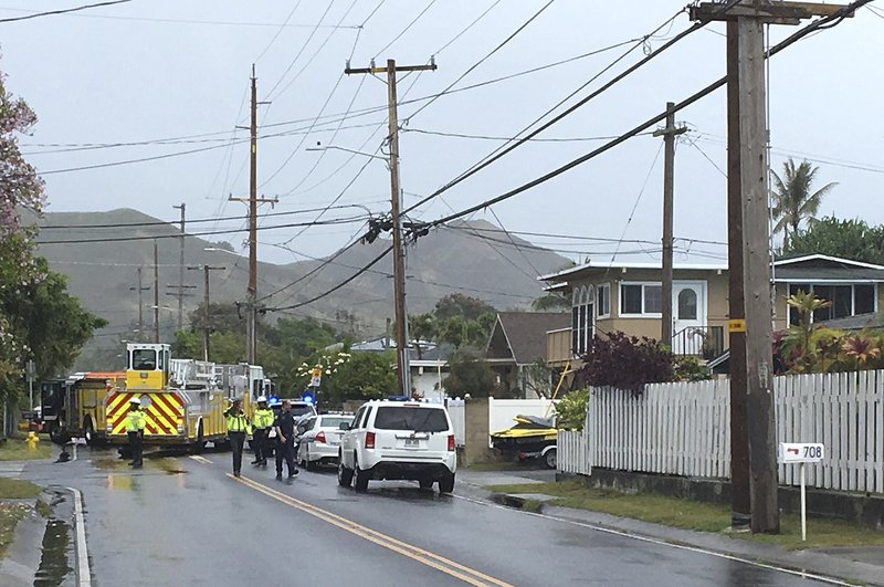 Police and firefighters respond to the scene of a helicopter crash in a residential neighborhood of Kailua, Hawaii, Monday, April 29, 2019. Fire and pieces of helicopter rained from the sky Monday in a suburban Honolulu community in a crash that killed three people aboard, officials and witnesses said. (AP Photo/Marco Garcia)