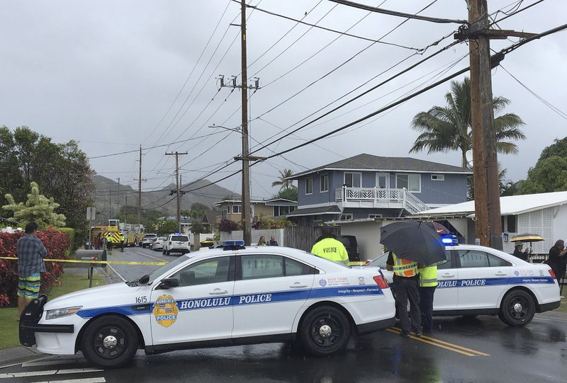 Police and firefighters respond to the scene of a helicopter crash in a residential neighborhood of Kailua, Hawaii, Monday, April 29, 2019. (AP Photo/Marco Garcia)