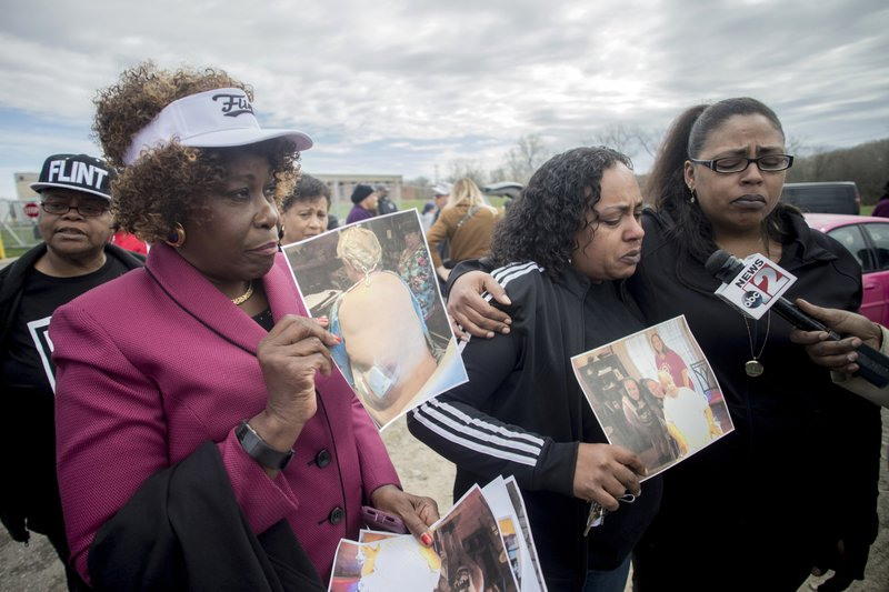 Detroit attorney Cynthia M. Lindsey stands alongside her clients Buffi Clements, 42 at center, and her sister Brandi as they talk about the death of their father Joseph C. (Jake May/MLive.com/The Flint Journal via AP)