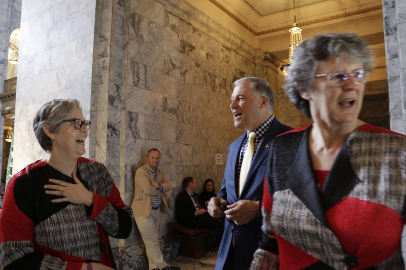 Democratic Rep. Laurie Jinkins, left, laughs while talking with Washington Gov. Jay Inslee, as fellow Democratic Rep. (AP Photo/Rachel La Corte)