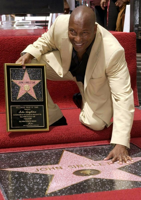 FILE - In this Aug. 26, 2003 file photo, director John Singleton touches his new star on the Hollywood Walk of Fame in Los Angeles. (AP Photo/Nick Ut, File)