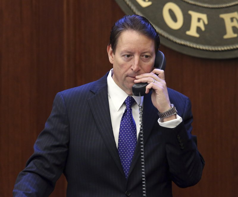Senate president Bill Galvano, R-Bradenton, multi tasks as he oversees the senate and talks on the phone during session Monday April 29, 2019, in Tallahassee, Fla. (AP Photo/Steve Cannon)