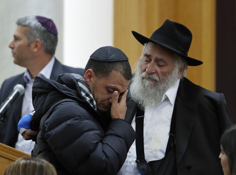 Rabbi Yishoel Goldstein, right, comforts Almog Peretz, center, Monday, April 29, 2019, as they attend the funeral for Lori Kaye, who was killed Saturday when a gunman opened fire inside the Chabad of Poway synagogue in Poway, Calif. (AP Photo/Gregory Bull)