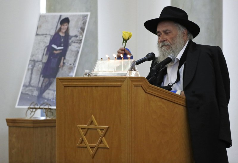 Yishoel Goldstein, Rabbi of Chabad of Poway, holds a yellow rose as he speaks Monday, April 29, 2019, at the funeral for Lori Kaye, who is pictured at left, in Poway, Calif. (AP Photo/Gregory Bull)