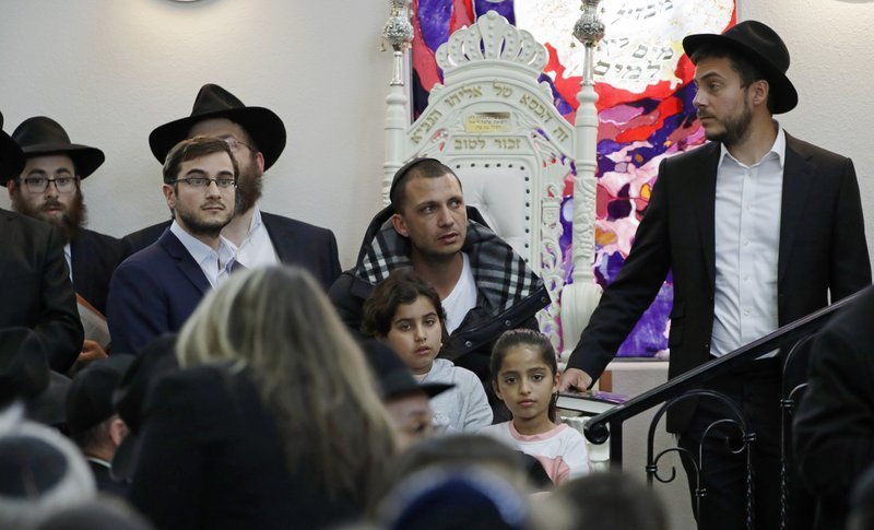 Almog Peretz, center, sits near his niece, Noya Dahan, 8, lower right, Monday, April 29, 2019, as they attend the funeral for Lori Kaye, who was killed Saturday when a gunman opened fire inside the Chabad of Poway synagogue in Poway, Calif. (AP Photo/Gregory Bull)
